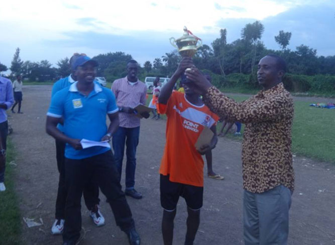 Guest of honor handing the trophy to the winning team